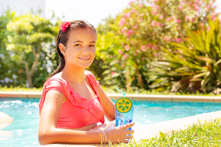 Happy girl in swimming pool with refreshing drink