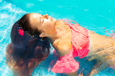 Beautiful young girl relaxing in swimming pool