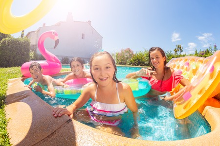 Happy girl relaxing with friends in swimming pool Stockfoto