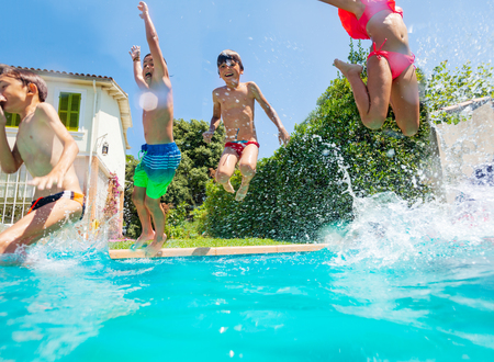 Happy friends jumping into the swimming pool