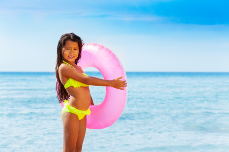 Asian girl with swim ring against exotic seascape 스톡 콘텐츠