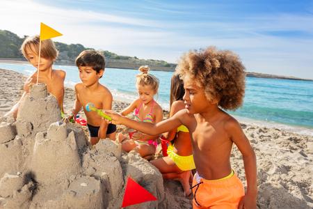 Kids creating sandcastle on the beach in summer Reklamní fotografie