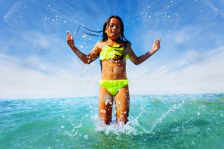 Joyful girl splashing while playing at the seaside Banco de Imagens - 114504835