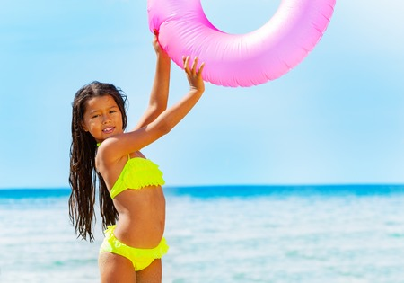 Asian girl with swim tube playing on the beach