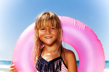 Cute little girl with pink swim ring on the beach