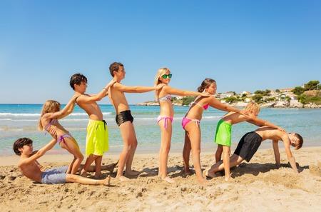 Gelukkige vrienden die in de zomer strandspelletjes spelen