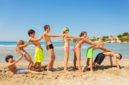 Happy friends playing beach games in summer Imagens