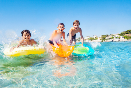 Three happy friends surfing the beach waves Stok Fotoğraf