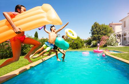 滑稽的少年拿着游泳工具跳进游泳池德赢体育