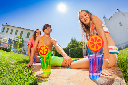 Friends spending summer by the pool with cocktails Stockfoto