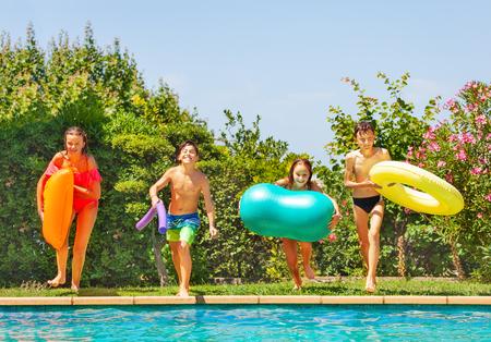 Kids preparing to jump into water of swimming pool