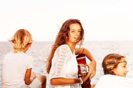 Girl singing with guitar for friends on the beach