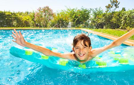 Boy having fun on air mattress in swimming pool