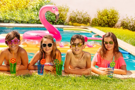 Happy friends with beverages on outdoor pool party Stockfoto