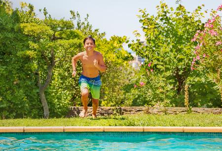 Happy teenage boy running to the swimming pool Reklamní fotografie - 114532709