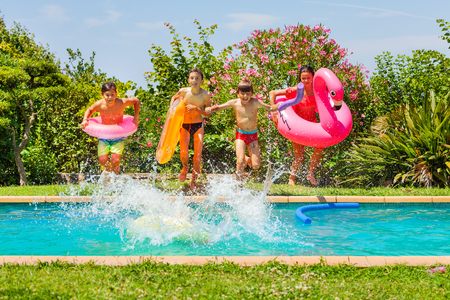 Cute kids jumping in swimming pool with swim rings Banco de Imagens - 114532757