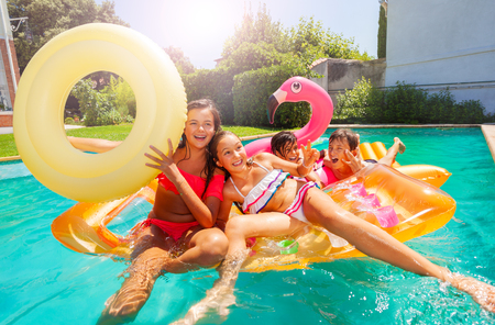 Happy teens playing with swimming floats in pool