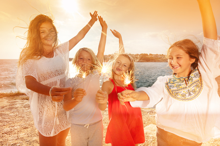 Teens having fun using sparklers on beach party