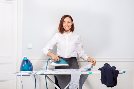 Woman ironing dress shirt before leaving for work