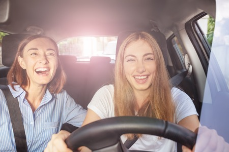 Girl and her mother having fun during road trip