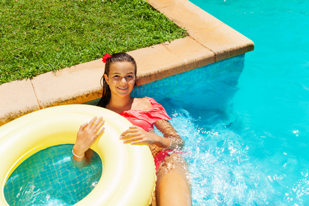 Girl relaxing in swimming pool with swim ring