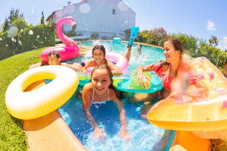 Joyful friends playing in outdoor swimming pool Standard-Bild
