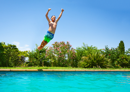 Cheerful boy jumping in outdoor swimming pool