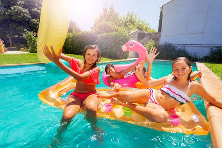 Happy friends lounging on pool floats in summer Stock fotó - 115350710