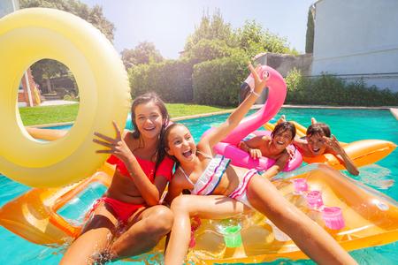 Adolescents mignons jouant avec des flotteurs de natation dans la piscine Banque d'images