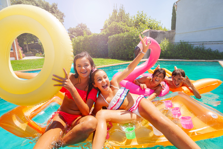 Cute teens playing with swimming floats in pool Imagens