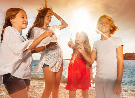 Happy teens holding sparklers during beach party