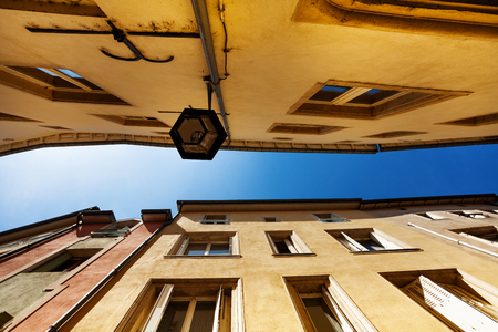 Outdoor lamp, roofs and sky on narrow old street