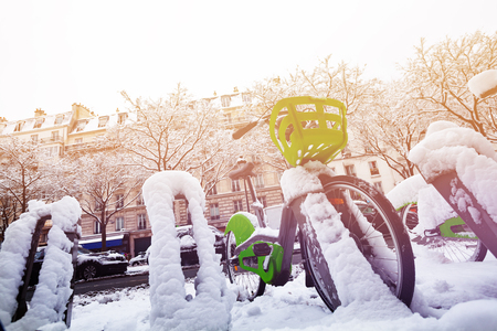 Paris bicycle parking at snowy winter day