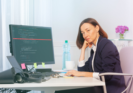 Sad businesswoman works on computer in the office