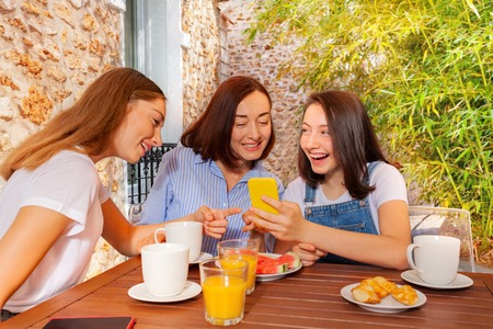 Girl having family breakfast and using smartphone 版權商用圖片