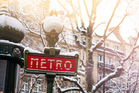 Famous Parisian metro sign covered with snow