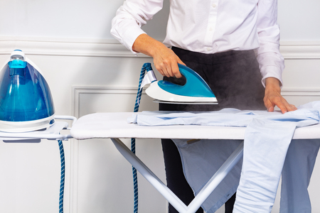 Womans hand holding steam iron and ironing shirt