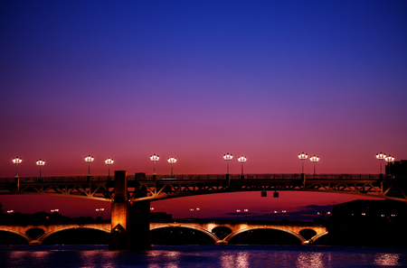 Garonne river embankment with illuminated bridges Stock Photo