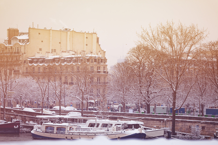 Seine river embankment and boats in snow, Paris Stock Photo