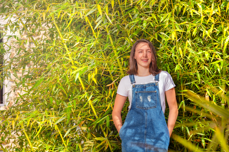 Lächelnde Teenager-Mädchen gegen grünen Bambusbusch