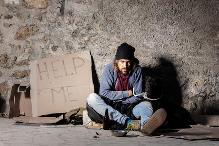 Hombre sin hogar sentado en la calle con un perro