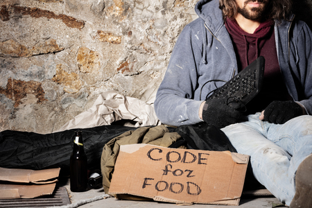 Jobless man sits with keyboard and cardboard sign Stock Photo