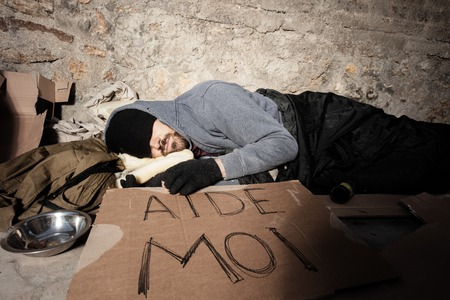 Homeless man in old clothes sleeping on the street