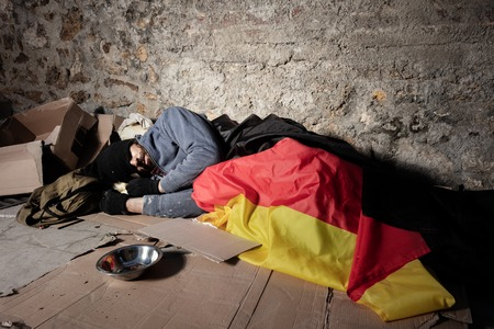 Man sleeping on the street under German flag