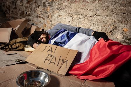 Homeless man sleeping outside under French flag
