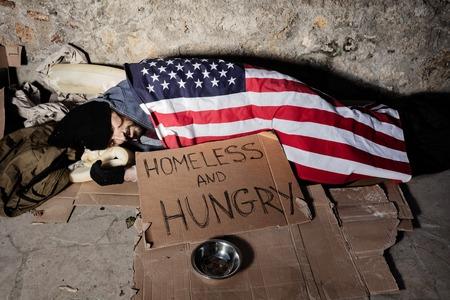 Hombre con cuenco de limosnas durmiendo bajo la bandera americana Foto de archivo