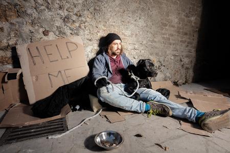 Tramp hugging his dog sitting on the city sidewalk
