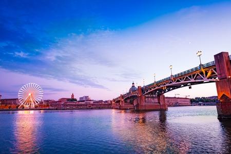 Bord de la Garonne avec grande roue au coucher du soleil