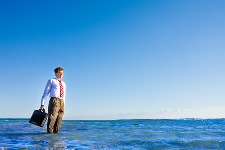 Young office white collar worker stand in the sea