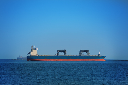 Dry cargo ship in the open sea against blue sky loaded with containers 写真素材